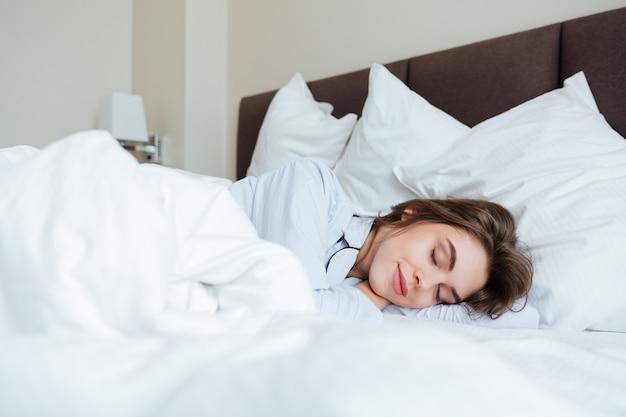 Jovem alegre, vestida de pijama, dormindo na cama