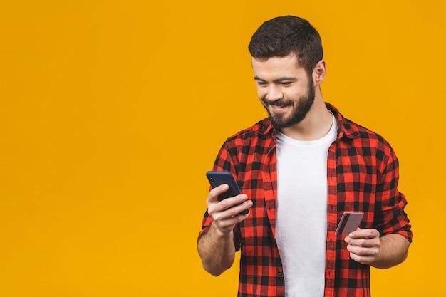 Jovem alegre vestindo camisa xadrez em pé isolado sobre a parede amarela, segurando o telefone móvel, mostrando o cartão de crédito plástico.