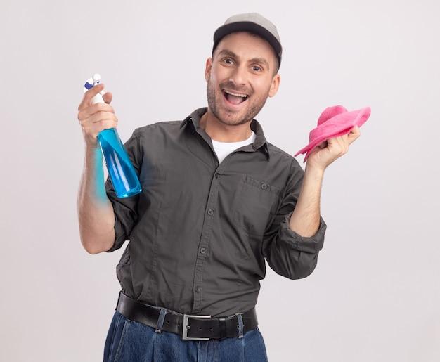 Jovem alegre, vestindo roupas casuais e boné, segurando o spray de limpeza e um pano, feliz e animado em pé sobre uma parede branca
