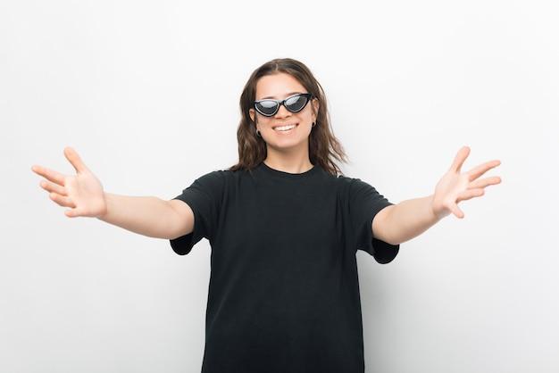 Jovem alegre vestindo uma camiseta preta fazendo um gesto de olá