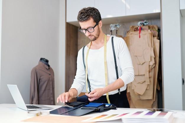 Jovem alfaiate de roupas casuais examinando amostras de tecidos enquanto trabalha em sua nova coleção de moda