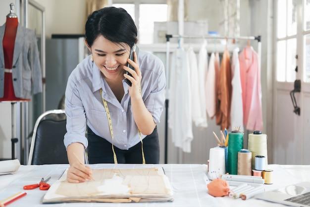 Jovem alfaiate design proprietário mulher falando com cliente