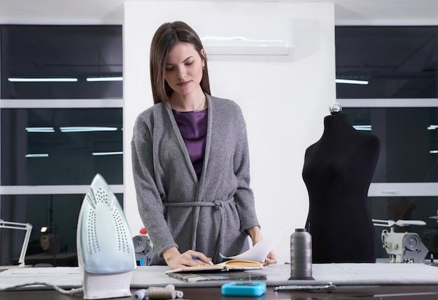 Jovem alfaiate em sua oficina de design de roupas novas