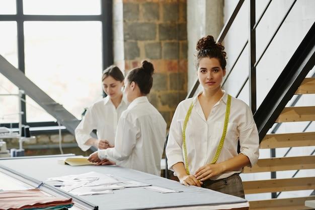 Jovem alfaiate feminina séria com fita métrica no pescoço, em pé junto à mesa na oficina com os colegas discutindo ideias nas proximidades