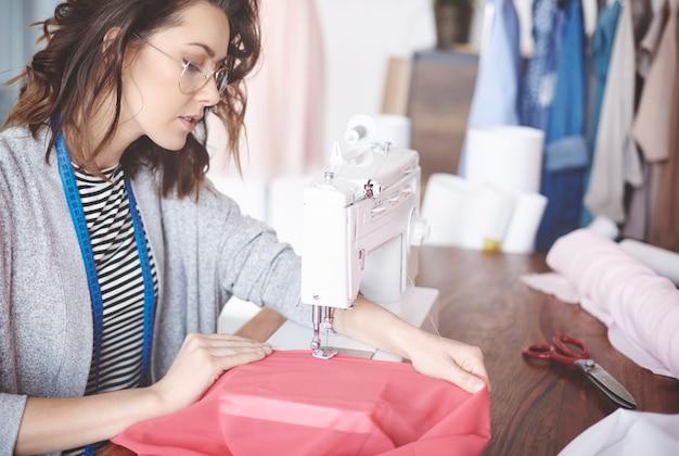 Jovem alfaiate habilidoso costurando na máquina