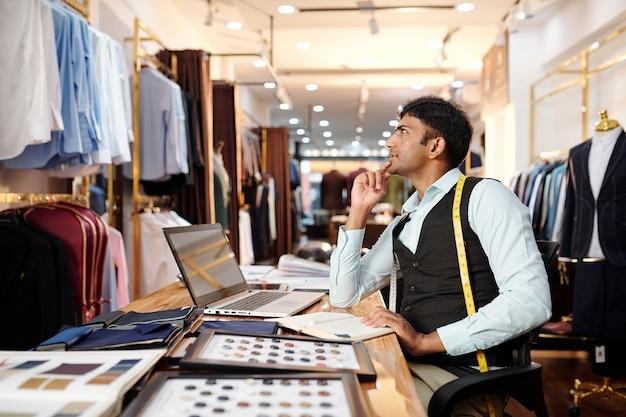 Jovem alfaiate indiano talentoso sentado à mesa grande no ateliê masculino pensando em um novo terno sob medida