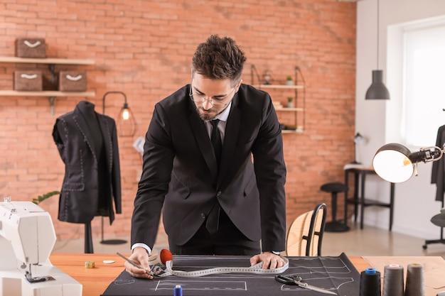 Jovem alfaiate trabalhando à mesa no ateliê
