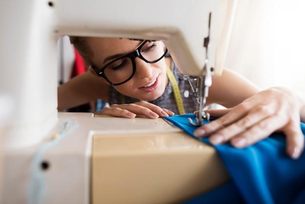 Jovem alfaiate trabalhando com máquina de costura