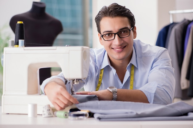 Jovem alfaiate trabalhando em roupas novas