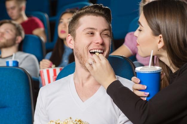 Jovem alimentando seu homem rindo alegre com pipoca no cinema