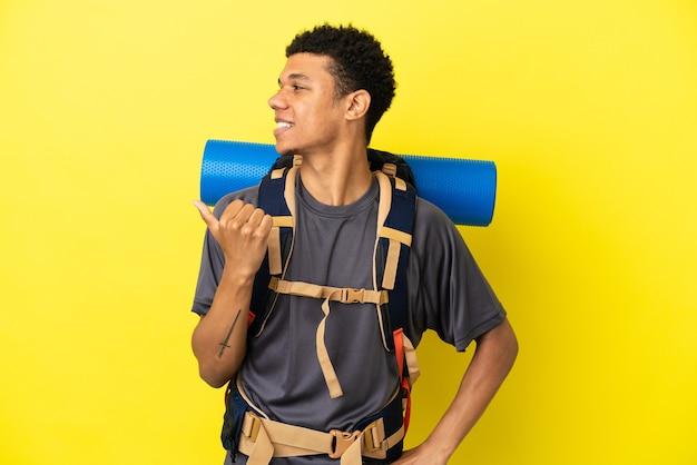 Jovem alpinista afro-americano com uma grande mochila isolada em um fundo amarelo apontando para o lado para apresentar um produto