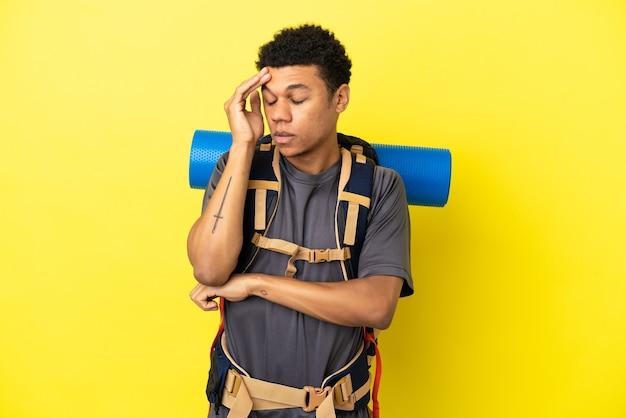 Jovem alpinista afro-americano com uma grande mochila isolada em um fundo amarelo com dor de cabeça