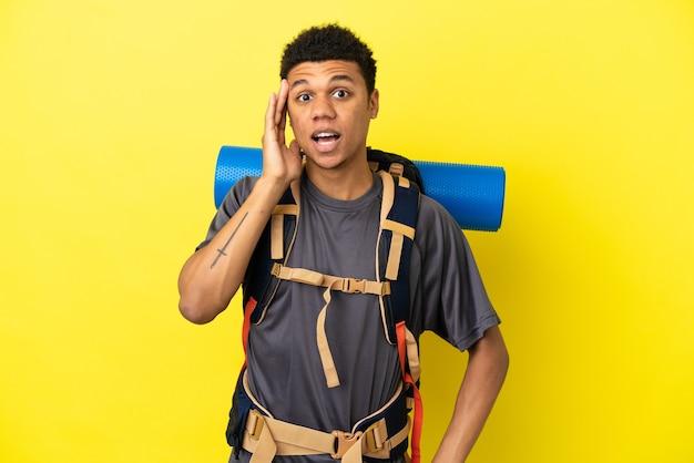 Jovem alpinista afro-americano com uma grande mochila isolada em um fundo amarelo com expressão facial de surpresa e choque