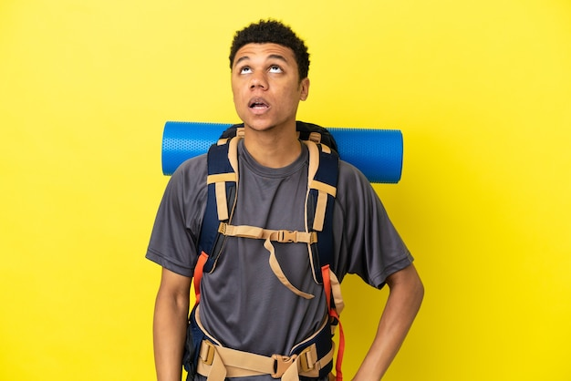 Jovem alpinista afro-americano com uma grande mochila isolada em um fundo amarelo, olhando para cima e com expressão de surpresa