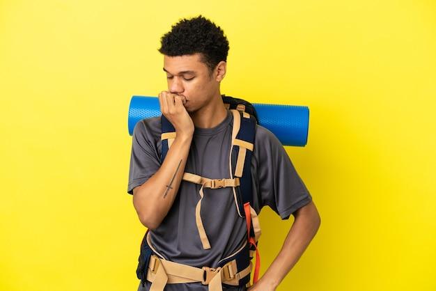 Jovem alpinista afro-americano com uma grande mochila isolada em um fundo amarelo, tendo dúvidas