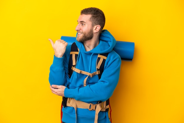 Jovem alpinista caucasiano com uma grande mochila isolada em um fundo amarelo apontando para o lado para apresentar um produto