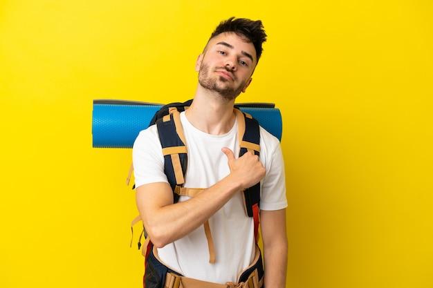 Jovem alpinista caucasiano com uma grande mochila isolada em um fundo amarelo orgulhoso e satisfeito