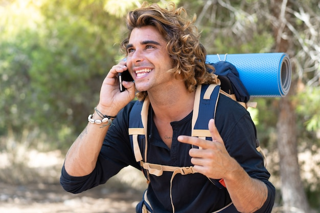 Jovem alpinista caucasiano passando as férias no acampamento e liga para os amigos