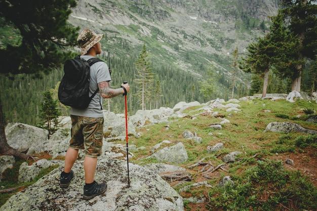 Jovem alpinista com mochila e trekking do penhasco e olhando para as montanhas no verão ao ar livre