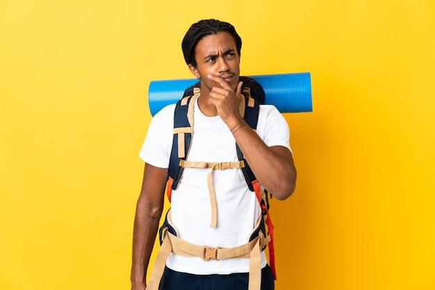 Jovem alpinista com tranças e uma grande mochila isolada em um fundo amarelo, tendo dúvidas