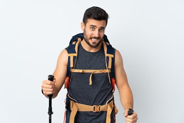 Jovem alpinista com uma grande mochila e bastões de trekking isolados no branco, tendo dúvidas com expressão facial confusa