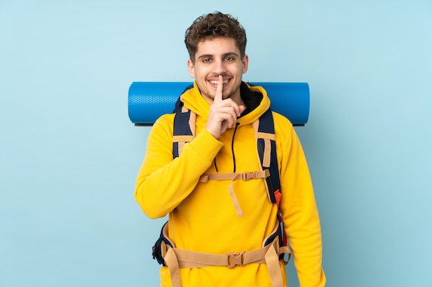 Jovem alpinista com uma grande mochila isolada em azul fazendo gesto de silêncio