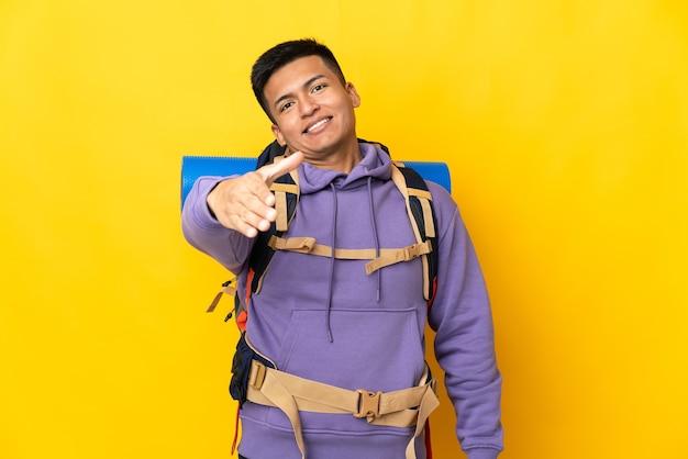 Jovem alpinista com uma grande mochila isolada em um fundo amarelo apertando as mãos para fechar um bom negócio Foto Premium