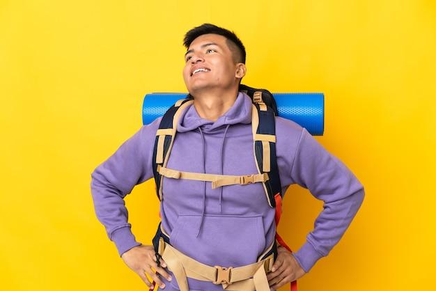 Jovem alpinista com uma grande mochila isolada em um fundo amarelo, posando com os braços na cintura e sorrindo