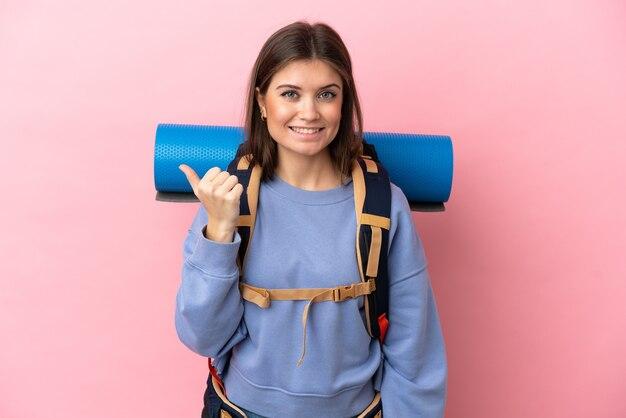Jovem alpinista com uma grande mochila isolada em um fundo rosa apontando para o lado para apresentar um produto