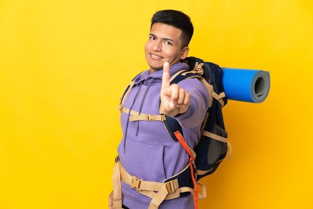 Jovem alpinista com uma grande mochila isolada na parede amarela, mostrando e levantando um dedo