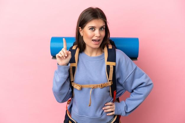 Jovem alpinista com uma grande mochila isolada pensando numa ideia apontando o dedo para cima