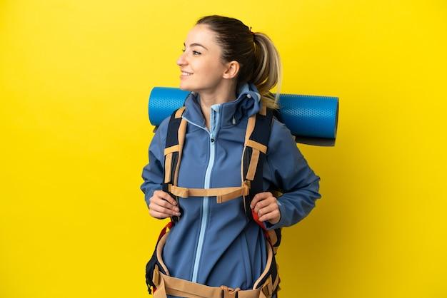 Jovem alpinista com uma grande mochila sobre um fundo amarelo isolado, olhando de lado