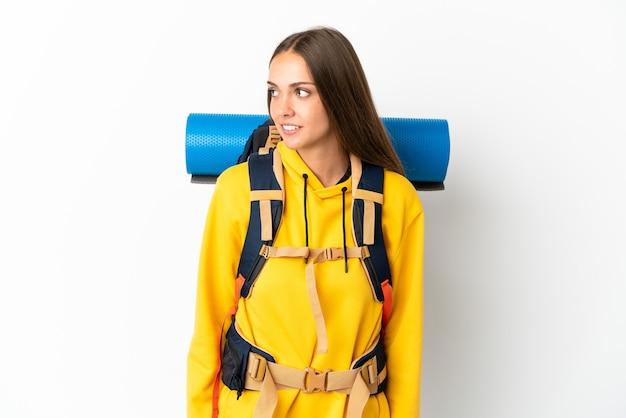Jovem alpinista com uma grande mochila sobre um fundo branco isolado, olhando de lado