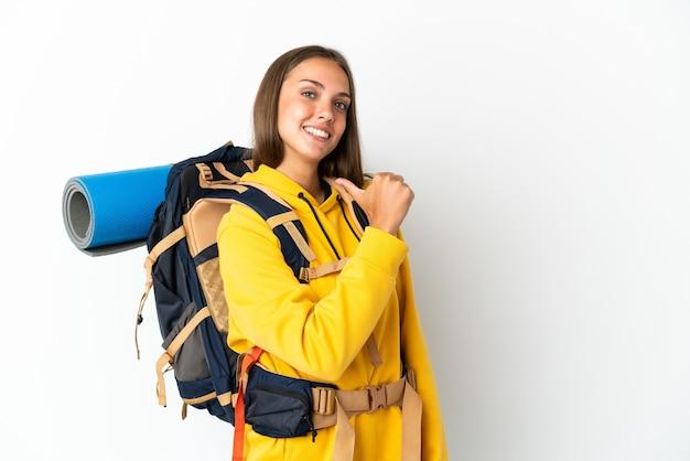 Jovem alpinista com uma grande mochila sobre um fundo branco isolado, orgulhosa e satisfeita