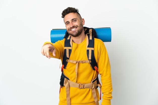 Jovem alpinista com uma grande mochila sobre um fundo isolado apontando para a frente com uma expressão feliz