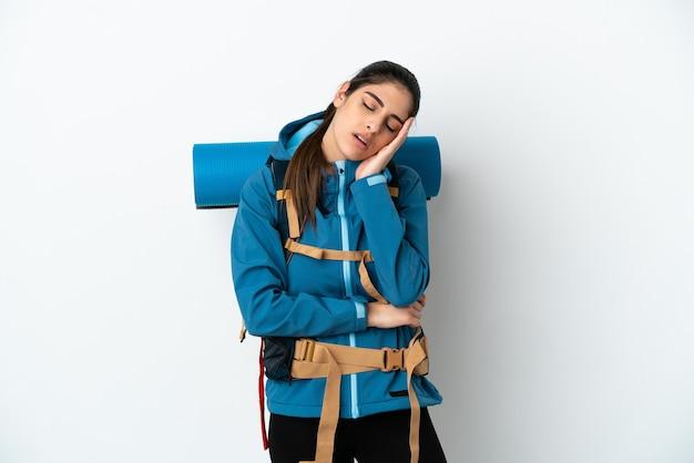 Jovem alpinista com uma grande mochila sobre um fundo isolado com dor de cabeça