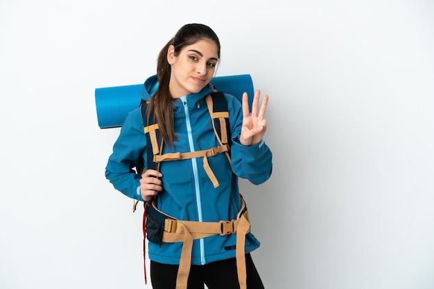 Jovem alpinista com uma grande mochila sobre um fundo isolado feliz e contando três com os dedos