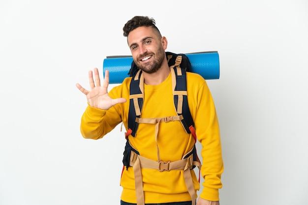Jovem alpinista com uma grande mochila sobre uma parede isolada, contando cinco com os dedos
