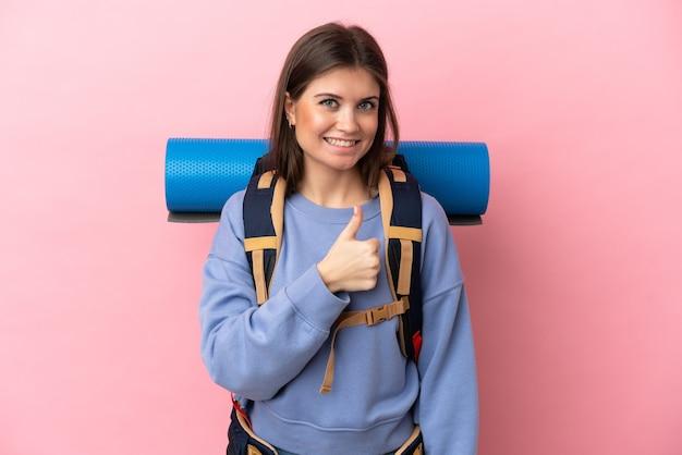 Jovem alpinista com uma mochila grande isolada em um fundo rosa e fazendo sinal de positivo