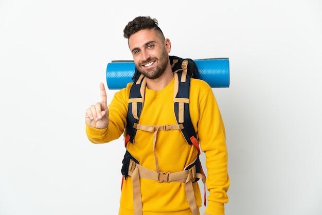 Jovem alpinista com uma mochila grande sobre um fundo isolado, mostrando e levantando um dedo