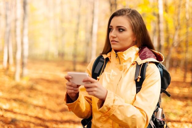 Jovem alpinista confuso com telefone inteligente na floresta