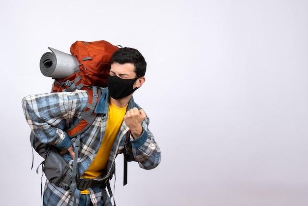 Jovem alpinista de frente com mochila e máscara colocando a mão nas costas com dor