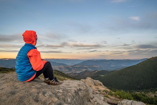 Jovem alpinista de menino sentado nas montanhas, apreciando a vista da paisagem de montanha incrível.