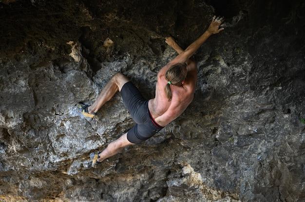 Jovem alpinista escalando uma parede rochosa em uma caverna