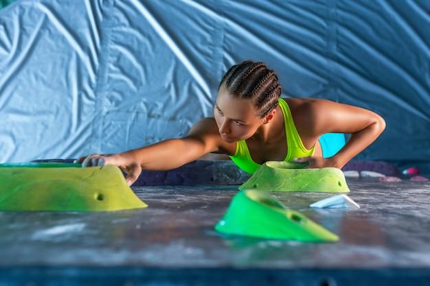 Jovem alpinista feminina atraente em um centro de treinamento propositadamente praticando escalar uma rocha em um pegboard - vista superior
