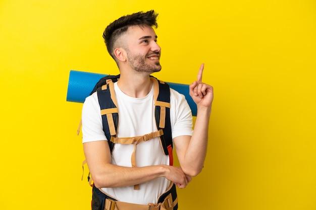 Jovem alpinista homem caucasiano com uma grande mochila isolada em um fundo amarelo apontando uma ótima ideia