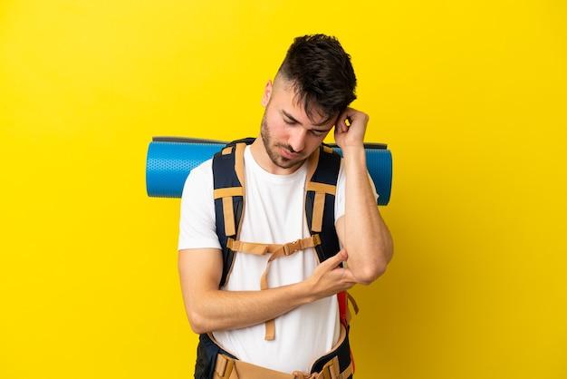 Jovem alpinista homem caucasiano com uma grande mochila isolada em um fundo amarelo com dor de cabeça
