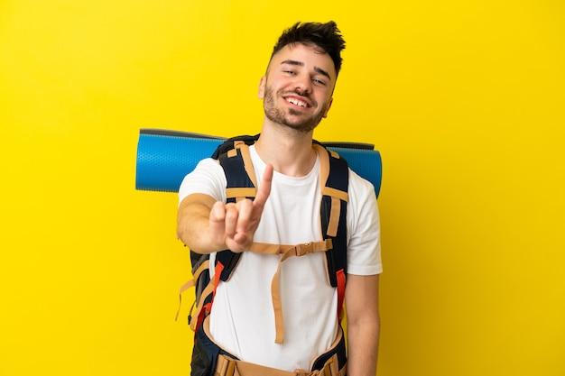 Jovem alpinista homem caucasiano com uma grande mochila isolada em um fundo amarelo, mostrando e levantando um dedo