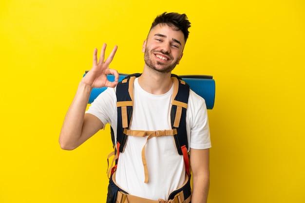 Jovem alpinista homem caucasiano com uma grande mochila isolada em um fundo amarelo, mostrando sinal de ok com os dedos