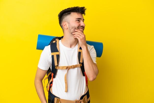Jovem alpinista homem caucasiano com uma grande mochila isolada em um fundo amarelo, olhando para cima enquanto sorri